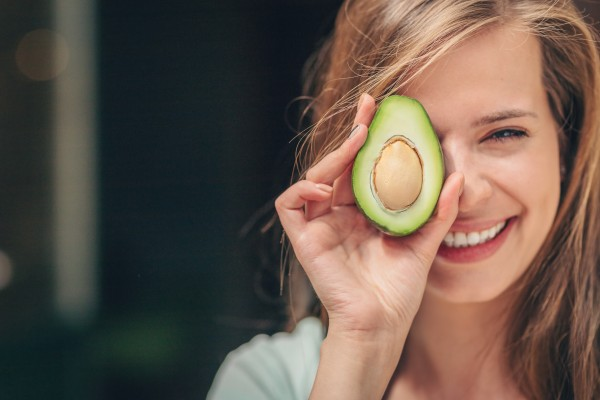 Coaching-Ernahrung_Vitamine-fur-Veganer_Beitragsbild_AdobeStock_216619258-Frau-mit-Avocado